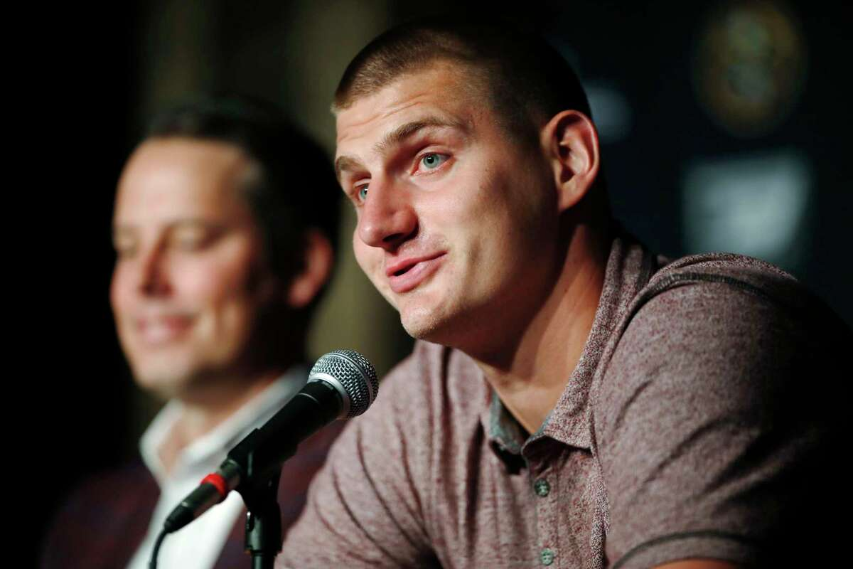 Denver Nuggets center Nikola Jokic, of Serbia, speaks with reporters as Josh Kroenke, president and governor of the Denver Nuggets, looks on during a news conference to outline a contract extension for Jokic and the re-signing of guard Will Barton by the NBA basketball team Monday, July 9, 2018, in Denver. (AP Photo/David Zalubowski)