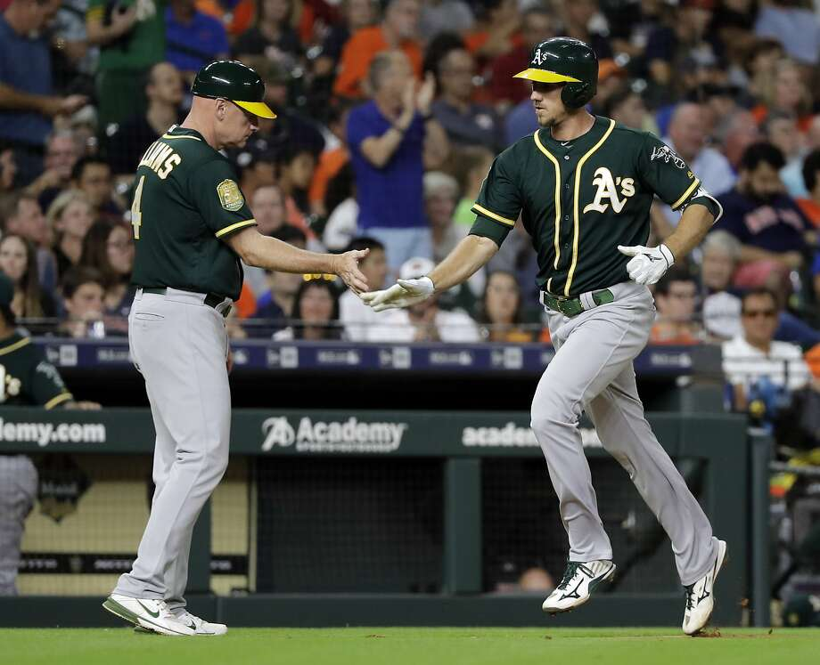 Oakland Athletics' Stephen Piscotty, right, is congratulated by third base coach Matt Williams (4) after hitting a home run against the Houston Astros during the seventh inning of a baseball game Monday, July 9, 2018, in Houston. Photo: David J. Phillip / Associated Press