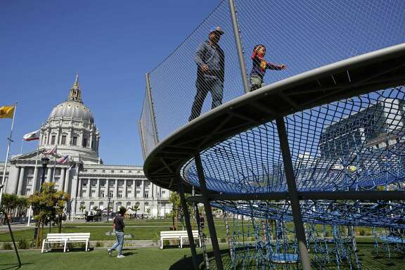 Nino Cunan and his 2-year-old son Kristopher enjoy the newly completed playgrounds in Civic Center Plaza in San Francisco on Tuesday, May 29, 2018. A bond measure is on the ballot that would fund city park improvements and maintenance.