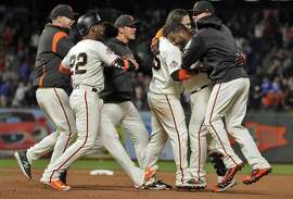 Pablo Sandoval is mobbed by teammates after hitting the game-winning single with the bases loaded in the 11th inning.