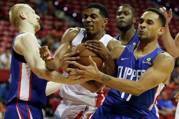 Los Angeles Clippers' Bogdan Bliznyuk, left, Houston Rockets' De'Anthony Melton, center, and and Los Angeles Clippers' David Michineau battle for the ball during the second half of an NBA summer league basketball game, Monday, July 9, 2018, in Las Vegas. (AP Photo/John Locher)