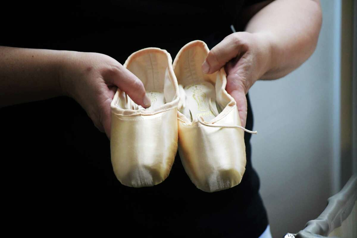 Marquerite Mehler, director of production for the New York City Ballet, shows a pair of ballet toe shoes that a dancer will wear during the New York City Ballet Saratoga season at Saratoga Performing Arts Center on Tuesday, July 10, 2018, in Saratoga Springs, N.Y. More than 1,000 toes shoes were shipped up to SPAC for the dancers. (Paul Buckowski/Times Union)