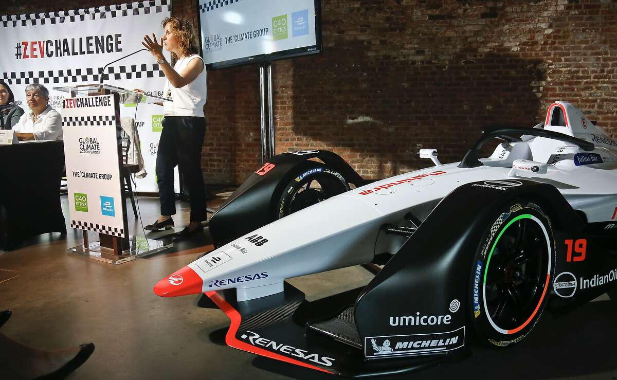 Helen Clarkson, CEO of The Climate Group, speaks next to a Generation 2 electric Formula-E racing car, during a panel discussion including Chairwoman of the California Air Resources Board Mary Dolores Nichols, left, Tuesday July 10, 2018, in New York. Clarkson announced a new initiative called Zero Emission Vehicle (ZEV) Challenge, that will see states, regions, cities and international business use their purchasing and policy influence to massively accelerate the adoption of electric vehicles around the world. The Formula E season finale auto race is Sunday in the Red Hook neighborhood in the borough of Brooklyn. (AP Photo/Bebeto Matthews)