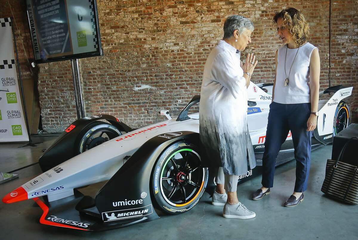 Helen Clarkson, right, CEO of The Climate Group, and Mary Dolores Nichols, left, Chairwoman of the California Air Resources Board, talks as they stand next to a Generation 2 electric Formula-E racing car, as they confer following a climate group panel discussion, Tuesday July 10, 2018, in New York. Clarkson announced a new initiative called Zero Emission Vehicle (ZEV) Challenge, that will see states, regions, cities and international business use their purchasing and policy influence to massively accelerate the adoption of electric vehicles around the world. The Formula E season finale auto race is Sunday in the Red Hook neighborhood in the borough of Brooklyn. (AP Photo/Bebeto Matthews)