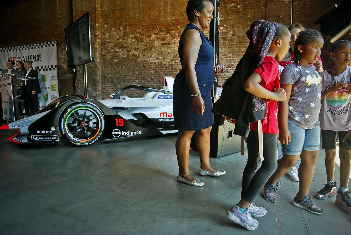 Summer camp youngsters leave after a brief viewing of a Generation 2 electric Formula-E racing car, following the announcement of a new initiative called Zero Emission Vehicle (ZEV) Challenge,Tuesday July 10, 2018, in New York. Helen Clarkson, CEO of The Climate Group, announced the ZEV Challenge, a program to accelerate the global adoption of electric vehicles, during a press conference and panel discussion. The Formula E season finale auto race is Sunday in the Red Hook neighborhood in the borough of Brooklyn. (AP Photo/Bebeto Matthews)