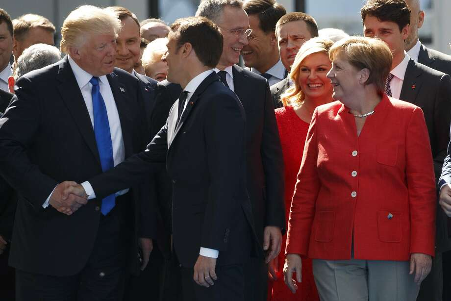 German Chancellor Angela Merkel (right) watches as President Trump shakes hands with French President Emmanuel Macron during a NATO ceremony last year in Brussels. Photo: Evan Vucci / Associated Press 2017