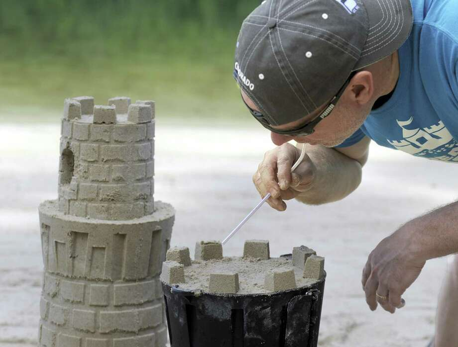 Kevin Lane uses a straw to blow excess sand from his sculpture Thursday morning, June 22, at Lynn Deming Park in New Milford. Lane of New Milford and his family invented a new system for building sand castles and snow sculptures. Photo: Carol Kaliff / Hearst Connecticut Media / The News-Times