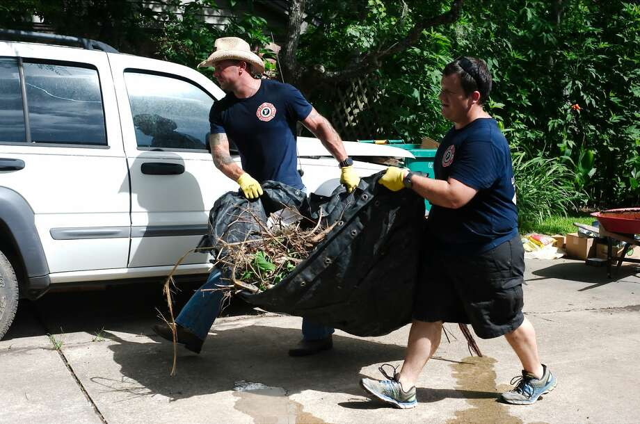 Pearland firefighters Jason Pecknold and Joshua Hendrix carry debris as the members of the Pearland Professional Firefighters Association volunteered Tuesday, Jul. 10 to assist Pearland resident Rosalea Nall  with the cleanup of her home damaged during Hurricane Harvey. Photo: Kirk Sides/Houston Chronicle