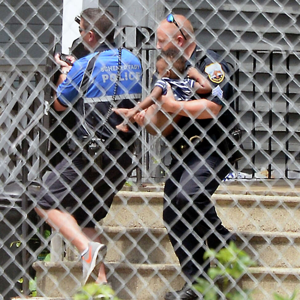 Police carry a small child from 1373 Union Street following the report of a shooting Tuesday July 10, 2018 in Schenectady, NY. (John Carl D'Annibale/Times Union)