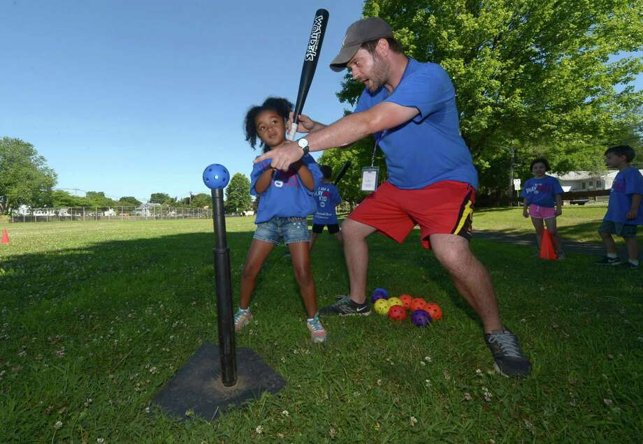 Counselor Ryan Perry instructs 5-year-old Sarai Richards on Tuesday, the first day of the Play Ball program of the Norwalk Recreation and Parks Play & Learn Summer Camps at Marvin Elementary School. The Norwalk Hour/Hearst Connecticut Media helped the city sponsor the Play Ball program for 650 children. Photo: Erik Trautmann / Hearst Connecticut Media / Norwalk Hour