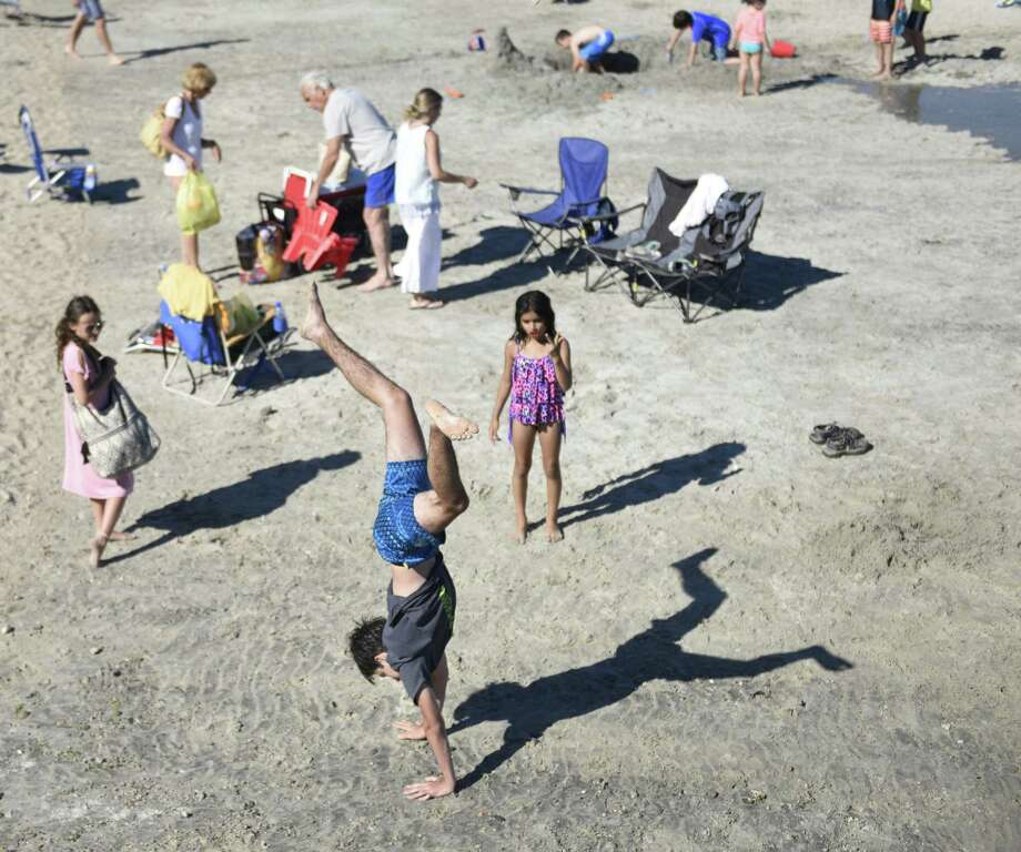 Greenwich's Hudson Moskowitz-Maione does a handstand on the beach at Greenwich Point Park in Old Greenwich, Conn. Saturday, July 7, 2018. Photo: Tyler Sizemore / Hearst Connecticut Media / Greenwich Time