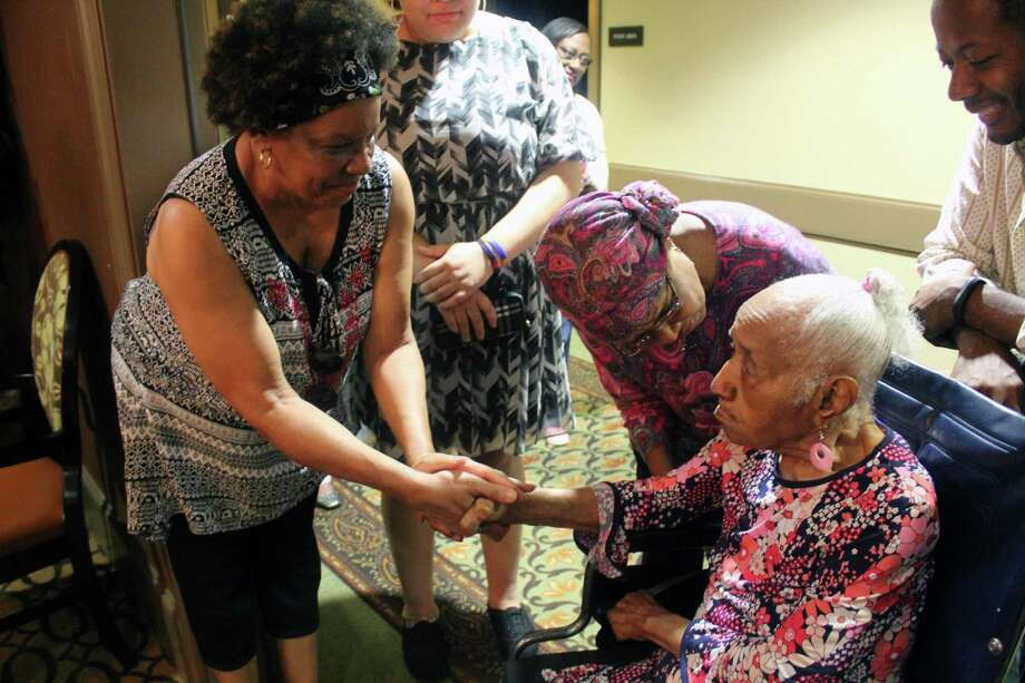Georgia Mitchell warmly holds the hands of guests as they greet her during her 104th birthday party at Landon Ridge in Kingwood on Sunday, July 8. Photo: Melanie Feuk / Melanie Feuk