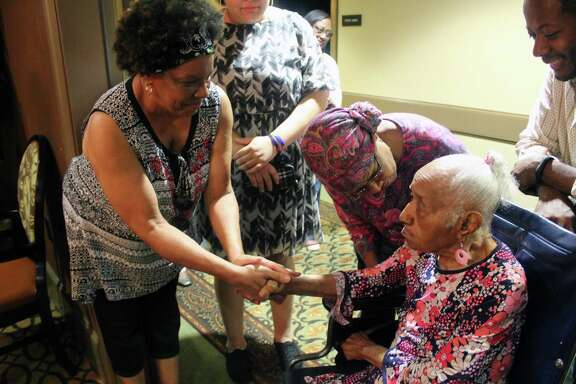 Georgia Mitchell warmly holds the hands of guests as they greet her during her 104th birthday party at Landon Ridge in Kingwood on Sunday, July 8.