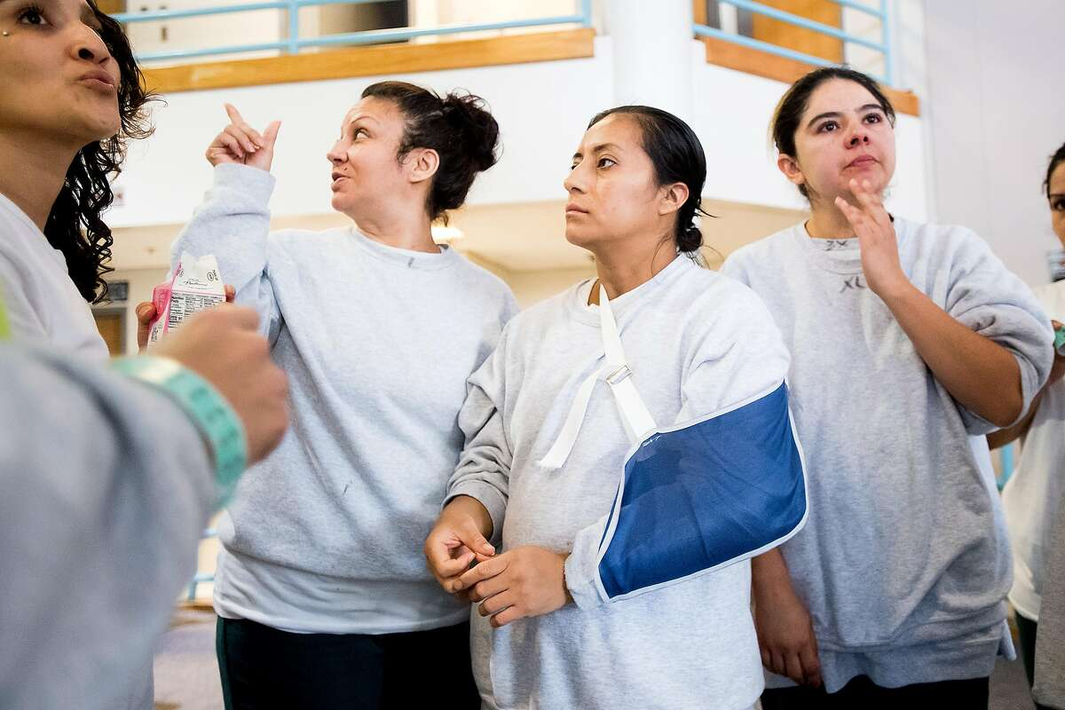 Ana Henriquez, center, and fellow Immigration and Customs Enforcement (ICE) detainees gather at the West County Detention Facility in Richmond, Calif., on Tuesday, Oct. 31, 2017.