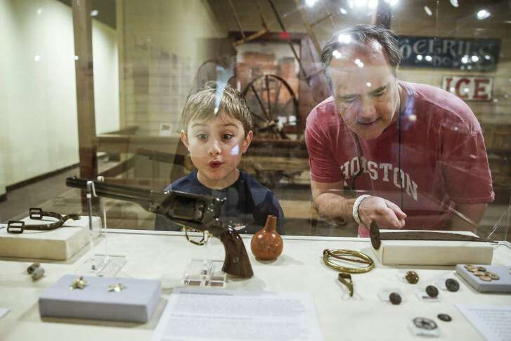 Caleb Nunez, 8, left, looks at a display case filled with Civil War artifacts with his father, Kevin Nunez, at the Houston in the Civil War exhibit at The Heritage Society.