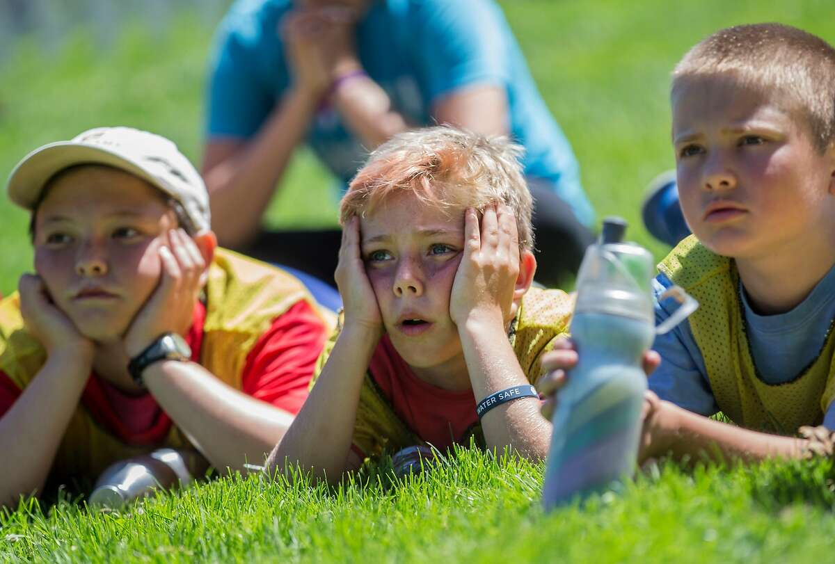 Members of the Bay City Soccer Club watch intensely as France and Belgium face off during the 2018 FIFA World Cup semi-finals watch party at Sue Bierman Park in San Francisco, Calif. Tuesday, July 10, 2018.