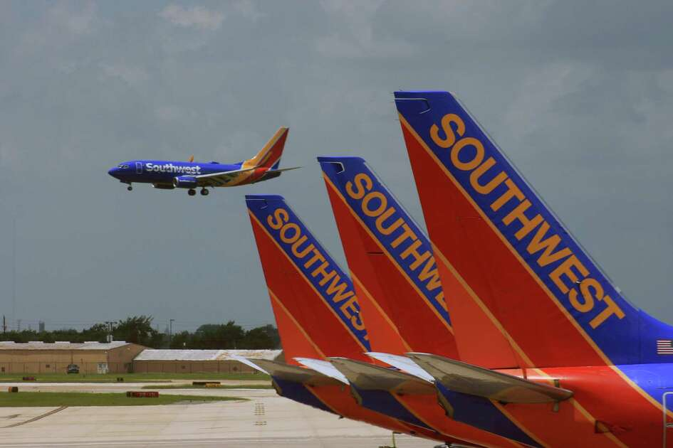 A Southwest Airlines Boeing 737 with the carrier's new paint job lands at Hobby Airport. The planes being prepared for departure from the international terminal sport the carrier's older paint scheme.