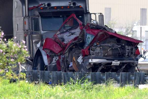 A mangled red truck is seen in front of a 18-wheeler at the scene of a wreck on Interstate 20 underneath the FM1788 overpass July 10, 2018., James Durbin/Reporter-Telegram