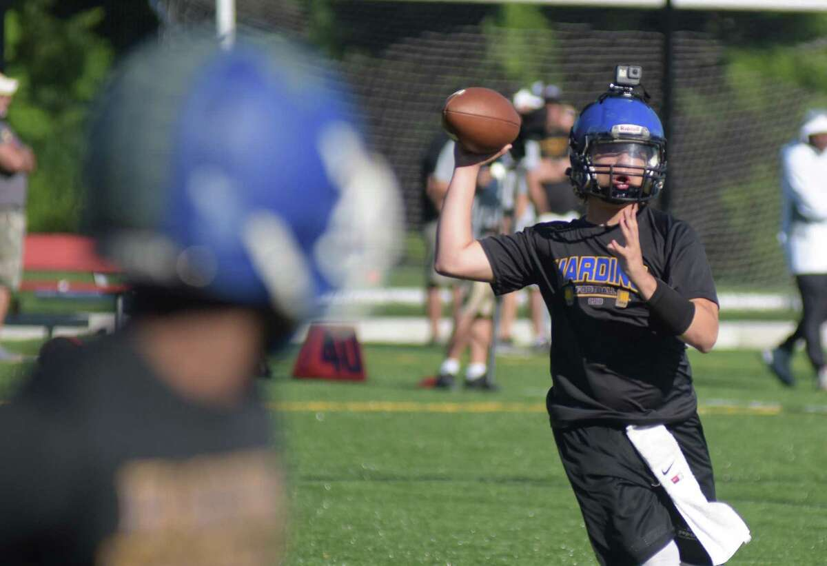 Harding quarterback Kevin Bednarz, right, looks to complete a pass with a Go-Pro camera on his head during Saturday's Grip It and Rip It 7-on-7 tournament in New Canaan.