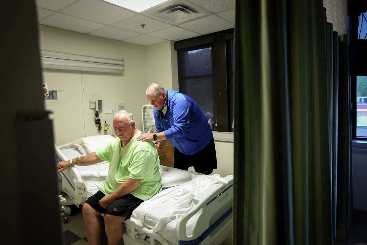 Dr. Van Breeding, director of medical affairs at a nonprofit clinic, examines a patient in Whitesburg, Ky. A federal judge has blocked Kentucky's plan to require many Medicaid recipients to work.