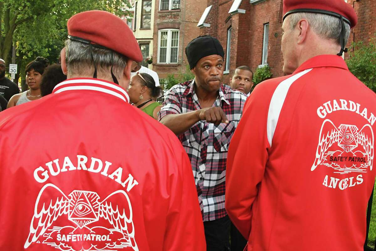 A resident lets Guardian Angel Founder Curtis Sliwa, right, know that he and his Guardian Angels are not wanted in their neighborhood as people gather at the corner of Clinton and Lexington Avenues in response to the recent spate in violence on Tuesday, July 10, 2018 in Albany, N.Y. (Lori Van Buren/Times Union)