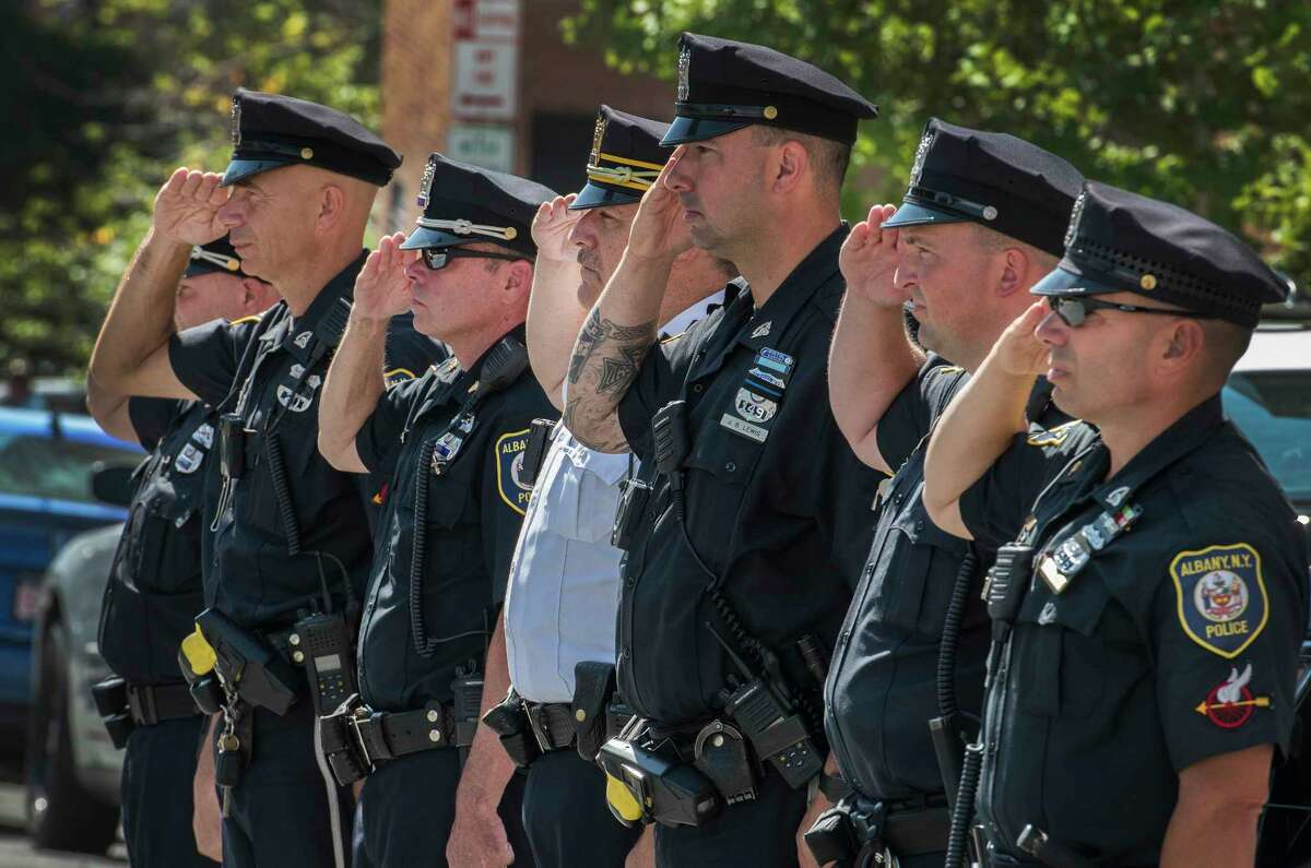 Members of the Albany Police Traffic Unit salute as the hearse carrying the remains of fallen Albany Police officer Dean Johnson leaves St. Mary's Church for the funeral service July 10, 2018 in Albany, N.Y. (Skip Dickstein/Times Union)