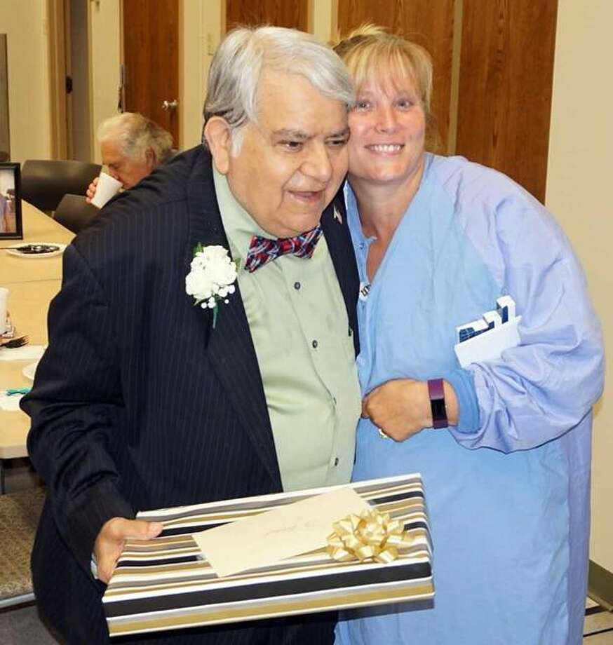 Dr. Noor Ahmed (left) is greeted by Shannon Dorks of the Alton Memorial Hospital Surgical Services Department during Dr. Ahmed's retirement party last month. Photo:       For The Telegraph