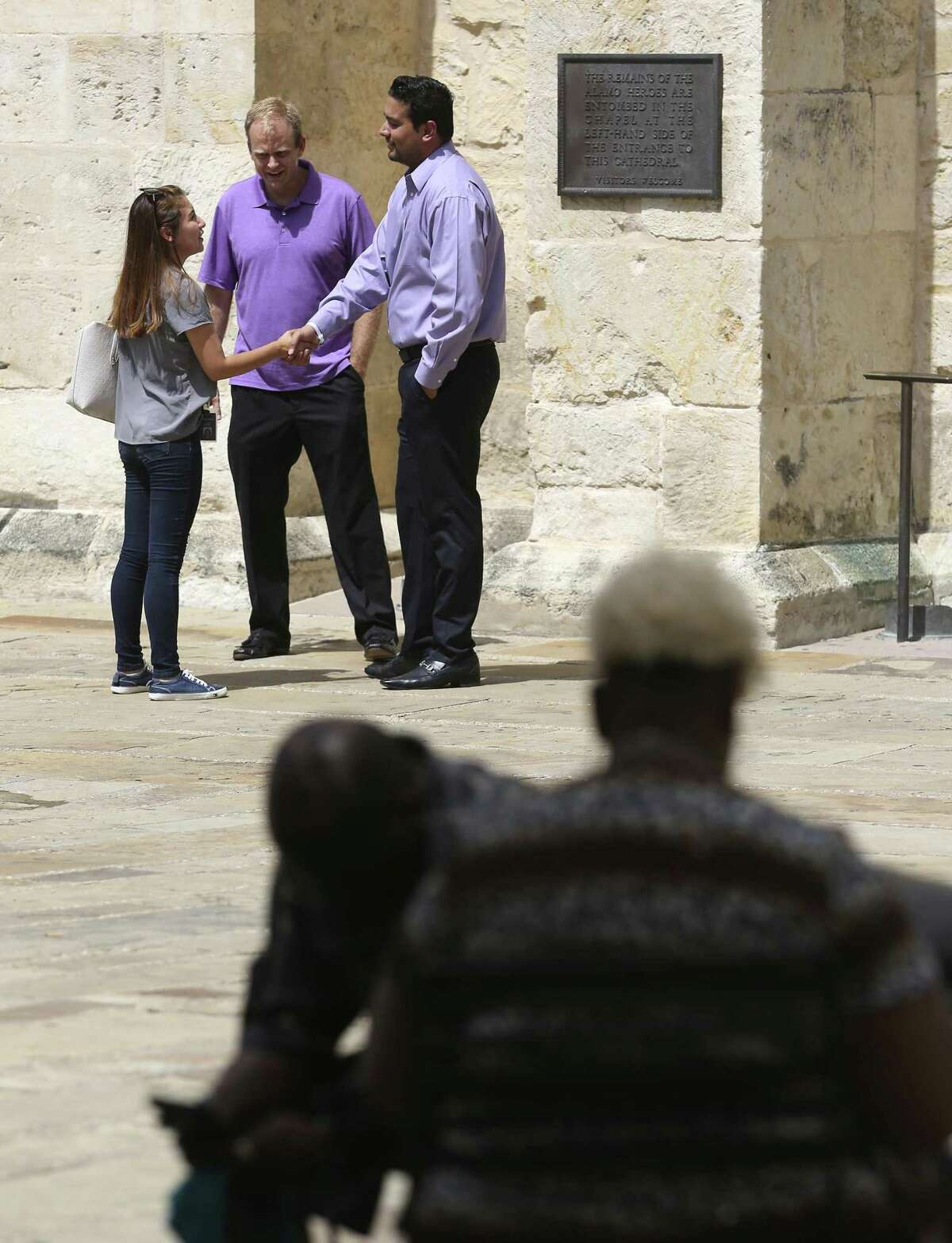 """Mitesh Patel, standing right, shakes hands with a reporter July 10, 2018, at Main Plaza while attorney Jeff Newberry listens to them. Patel is the son of 2004 murder victim, Hasmukh """"Hash"""" Patel, whose killer, Christopher Anthony Young, is scheduled to be executed July 17. The younger Patel was in Main Plaza to show support for the people holding a news conference urging clemency for Young."""
