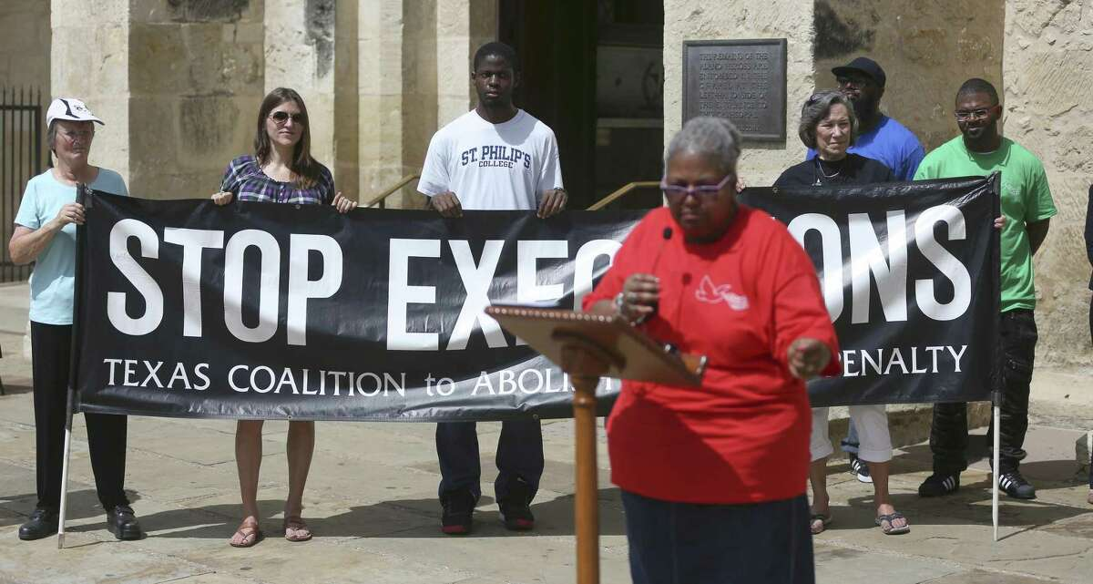 """People hold a banner July 10, 2018, that says """"Stop executions"""" during a news conference at Main Plaza, calling attention to clemency efforts being undertaken for Christopher Anthony Young, scheduled to be executed July 17 for the 2004 murder of Hasmukh """"Hash"""" Patel. Speaking at the lectern is Christopher Young's aunt, Valerie Harris."""