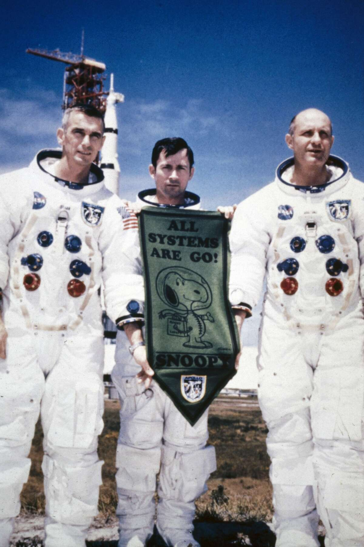 UNITED STATES - JUNE 25: Left to right; Eugene Cernan, John Young and Thomas Stafford standing in spacesuits in front of the Saturn V rocket carried the Apollo 10 spacecraft. Young is holding a pennant with the legend ?All Systems Are Go!? and a cartoon of Snoopy in a spacesuit. The Apollo 10 Lunar Module was codenamed Snoopy and the Command Module Charlie Brown. Apollo 10 was launched on 18th May 1969 on a lunar orbital mission, the dress rehearsal for the Apollo 11 moon landing mission which took place two months later. (Photo by SSPL/Getty Images)