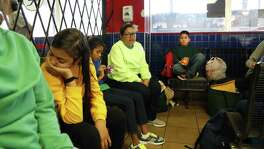Jade Cardoza, 13, from Honduras waits with her mother, far left out of the frame, after being released. In background is Celma Turcios ,yellow shirt,with her son Wilmer Bajurto,10 who she was separated for one day at McAllen. Trying on multiple fronts to get photos about immigrant parents getting their children back. on Tuesday, July 10, 2018.