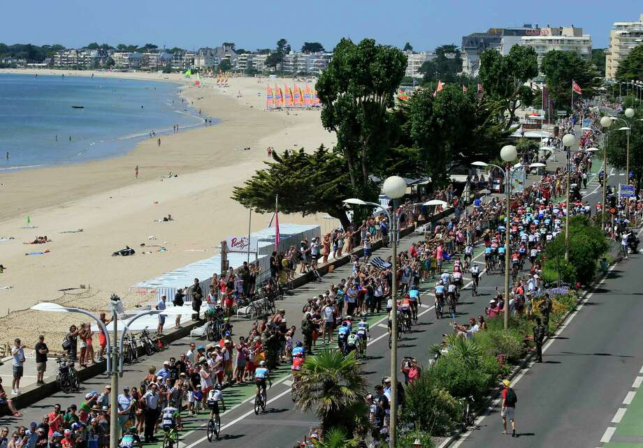 The pack rides along the beach in La baule during the fourth stage of the Tour de France cycling race over 195 kilometers (121 miles) with start in La Baule and finish in Sarzeau, France, Tuesday, July 10, 2018. (AP Photo/Peter Dejong) Photo: Peter Dejong / Copyright 2018 The Associated Press. All rights reserved
