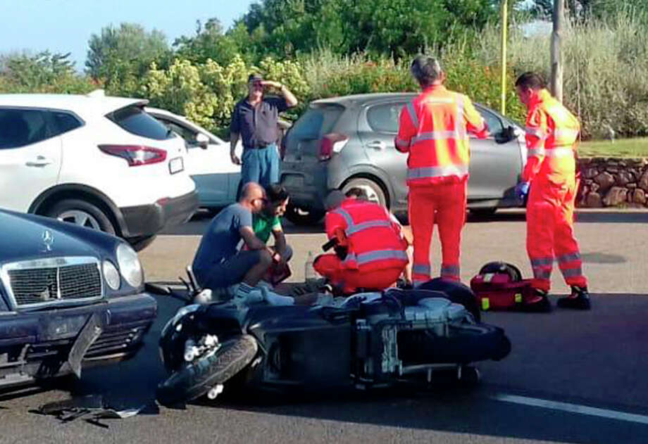 """Ambulance personnel tend to a man lying on the ground, later identified as actor George Clooney, after being involved in a scooter accident in the near Olbia, on the Sardinia island, Italy, Tuesday, July 10, 2018. Actor George Clooney was taken to the hospital in Sardinia on Tuesday and released after being involved in an accident while riding his motor scooter, hospital officials said. """"He is recovering at his home and will be fine,"""" spokesman Stan Rosenfield told The Associated Press in an email. The John Paul II hospital in Olbia confirmed Clooney had been treated and released after Tuesday's accident. Local media that had gathered at the hospital said Clooney left in a van through a side exit. (AP Photo/Mario Chironi) Photo: Mario Chironi / Mario Chironi"""