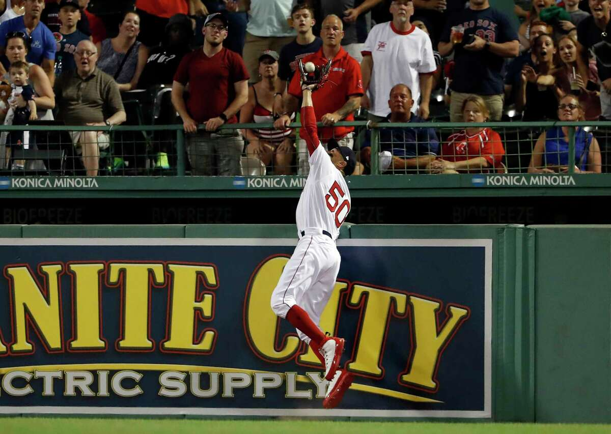 Boston Red Sox right fielder Mookie Betts reaches over the wall to catch a ball hit by Texas Rangers' Nomar Mazara during the fifth inning of a baseball game Tuesday, July 10, 2018, in Boston. (AP Photo/Winslow Townson)