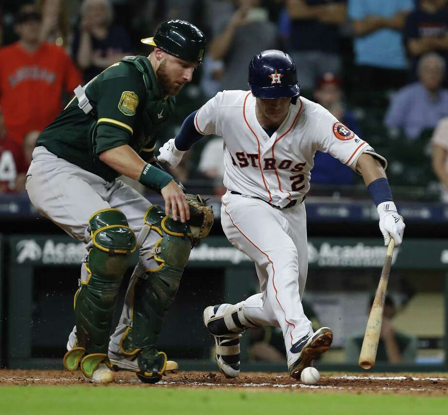 Houston Astros Alex Bregman (2) watches the ball with Oakland Athletics catcher Jonathan Lucroy (21) as Bregman reached on a single allowing Kyle Tucker to score the winning run during the eleventh inning of an MLB game at Minute Maid Park, Tuesday, July 10, 2018, in Houston. ( Karen Warren  / Houston Chronicle ) Photo: Karen Warren, Staff / Houston Chronicle / © 2018 Houston Chronicle