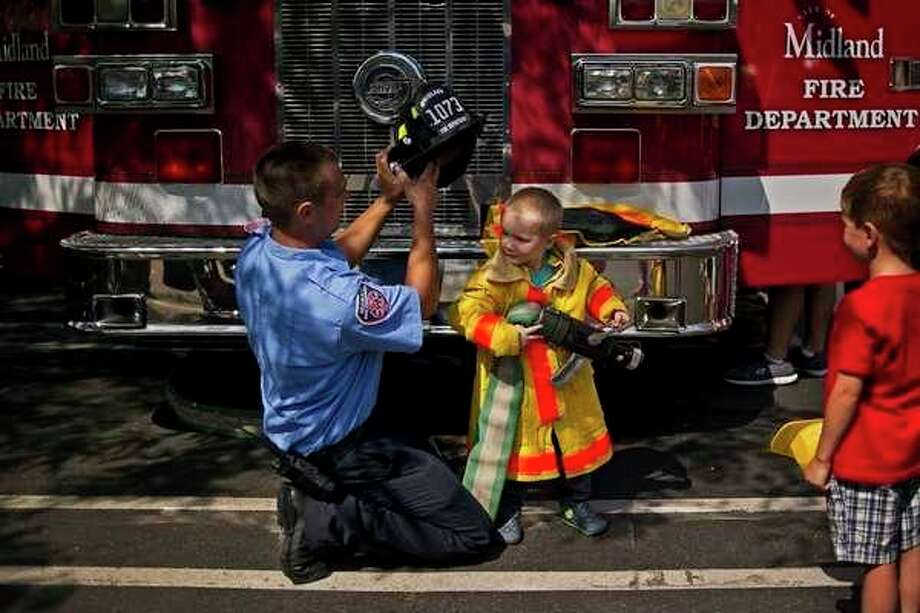 A youngster enjoys a moment as a firefighter at a previous Touch a Truck event in Midland. (File photo)