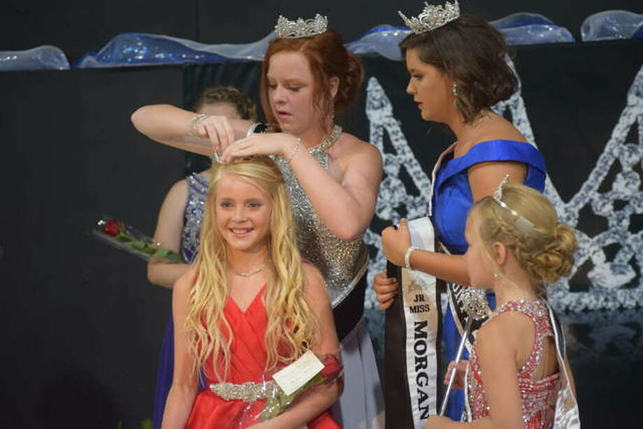 Junior Miss Morgan County Bella Evans is crowned by former Junior Miss Morgan County Camille Brown and former Queen Gracie Richardson.