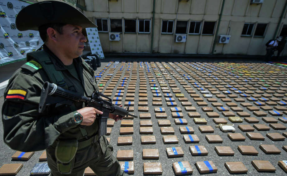 A member of the Colombian antinarcotics police, stands guard beside a one-ton shipment of cocaine seized to the country's biggest drug gang, the Gulf Clan in a container with destination to Europe in Buenaventura, Colombia's main port on the Pacific Ocean, on August 10, 2017. Photo: AFP Contributor/AFP/Getty Images