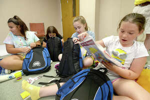 Children, including (from right) Reese Warwick, 9, Shayne Pannell, 10, Lauraianna Barnett, 10, and Elena Salinas, 10, dig into backpacks filled with disaster preparedness kits and helpful information during Camp Noah at North Orange Baptist Church. The program is helping children deal with the ongoing effects of emotional trauma experienced during Harvey last year. Area schools identified children who were impacted by Harvey, nominating them for the camp, which is being run by members of 2 Lutheran churches in Minnesota. Children are learning ways to prepare for emergencies, and stay safe, as well as cope with the feelings experienced during such disasters. Tuesday, July 10, 2018 Kim Brent/The Enterprise