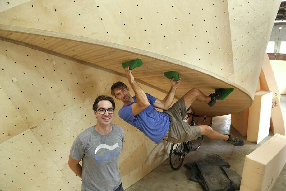 Michael Cano (left) and Joe Kreidel demonstrate the curved climbing wall at their near-complete Armadillo Boulders. Photo: Ronald Cortes /Photo Correspondent / 2018 Ronald Cortes