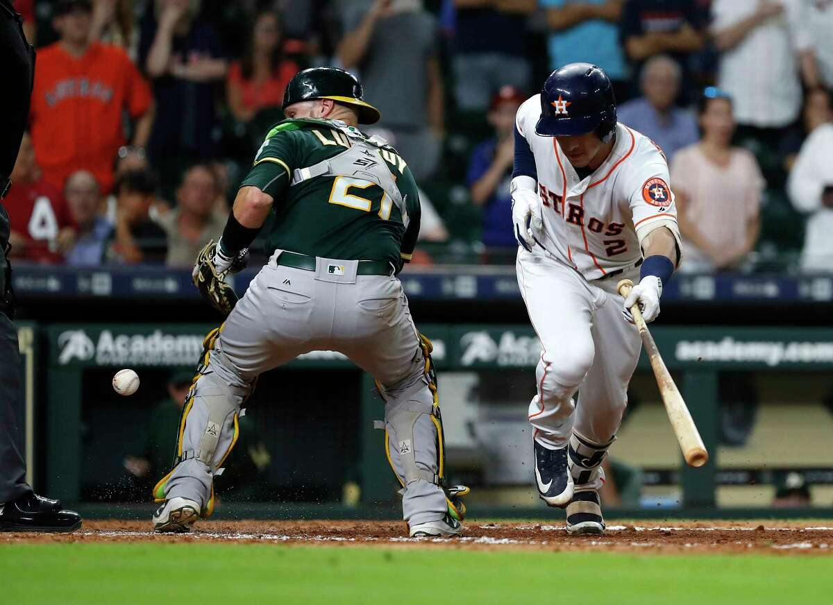 Oakland Athletics catcher Jonathan Lucroy loses control of the ball as Houston Astros Alex Bregman breaks for first base during the eleventh inning of an MLB game at Minute Maid Park, Tuesday, July 10, 2018, in Houston.