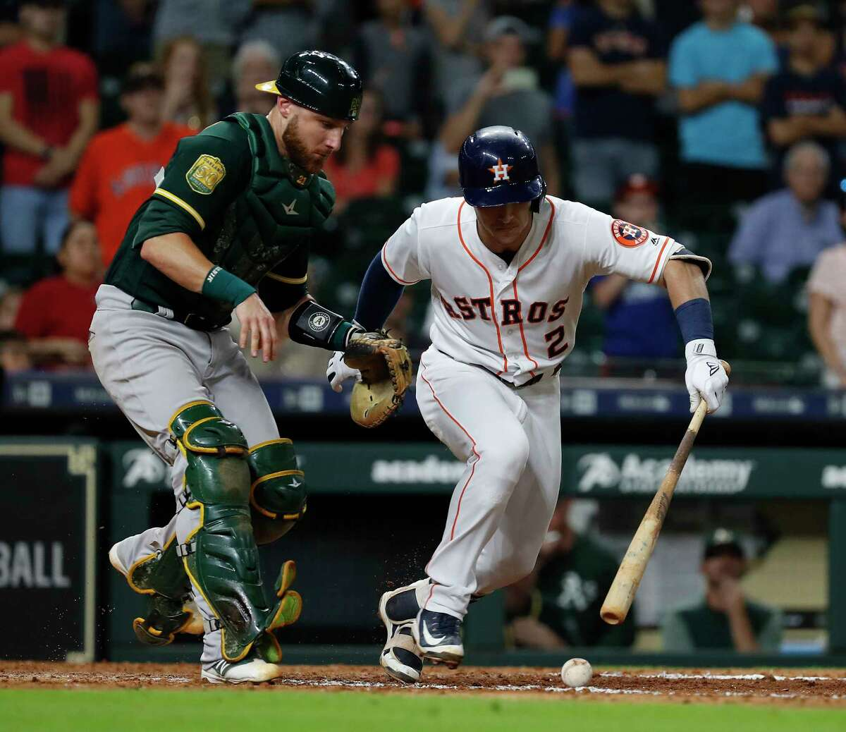Houston Astros Alex Bregman (2) breaks down the line as Oakland Athletics catcher Jonathan Lucroy reaches for the dribbler during the eleventh inning of an MLB game at Minute Maid Park, Tuesday, July 10, 2018, in Houston.