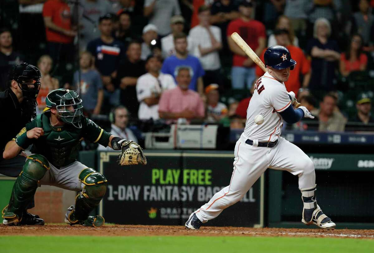 Houston Astros Alex Bregman (2) swings at the ball as Oakland Athletics catcher Jonathan Lucroy reacted during the eleventh inning of an MLB game at Minute Maid Park, Tuesday, July 10, 2018, in Houston.