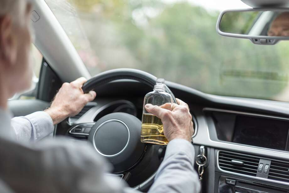 A Florida man insisted he wasn't drinking and driving, and told police he was only taking swigs from the bottle of bourbon tossed on the passenger's seat at stop signs and traffic lights and not when the car was moving. Photo: Thodonal/Getty Images/iStockphoto