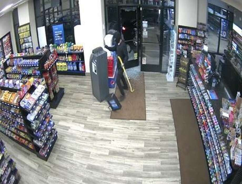 A man dressed in black and wearing a ski mask used a yellow crowbar to smash the front door of the Mobil Mart on Bridgeport Avenue on Monday, July 9, 2018. The suspect then stealed an ATM machine and but in the back seat of a waiting vehicle. Photo: Milford Police Department Photo