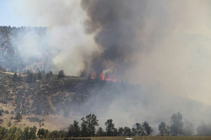 In this photo taken Thursday, July 5, 2018, the Klamathon Fire burns near Copco Road in Hornbrook, Calif. The wildfire burning through drought-stricken timber and brush near California's border with Oregon has killed one person and destroyed multiple structures as it grows largely out of control, authorities said Friday. (Danielle Jester/Siskiyou Daily News via AP)