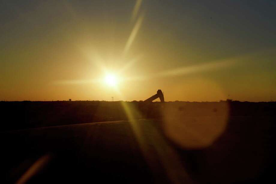 The sun sets behind an oil rig seen from Monahans Sandhills State Park in Monahans, Texas, U.S., on Tuesday, June 19, 2018. Two Permian Basin counties were among the top 10 in the state for those that received the most value in their property taxes, according to a study by SmartAsset.com. Photo: Callaghan O'Hare, Bloomberg / © 2018 Bloomberg Finance LP