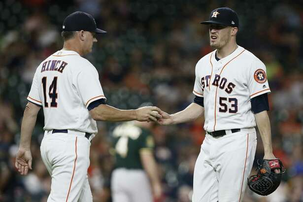 HOUSTON, TX - JULY 10: Manager AJ Hinch #14 of the Houston Astros takes the ball from Ken Giles #53 in the ninth inning against the Oakland Athletics at Minute Maid Park on July 10, 2018 in Houston, Texas.