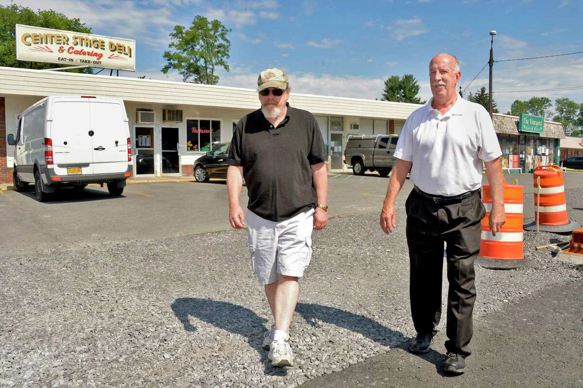 Liquor store owner Tom Vincent, left, and Deli owner David Kniskern look over road construction in front of their businesses along Hamburg Street Tuesday July 10, 2018 in Rotterdam, NY. (John Carl D'Annibale/Times Union)