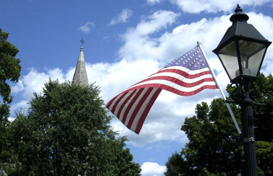 File photo of the American flag along Main Street in New Milford with the steeple of St. John's Episcopal Church in the background. Photo: Norm Cummings / Norm Cummings / The News-Times